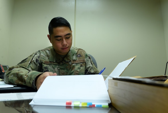 Airman sits at desk looking a file.