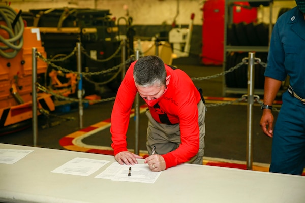 Lt. Cmdr. Paul Castillo, USS Gerald R. Ford's Ordnance Handling Officer, signs turnover paperwork to take possession of Lower Stage Weapons Elevator Lower Stage Weapons Elevator (LSWE), July 22, 2020