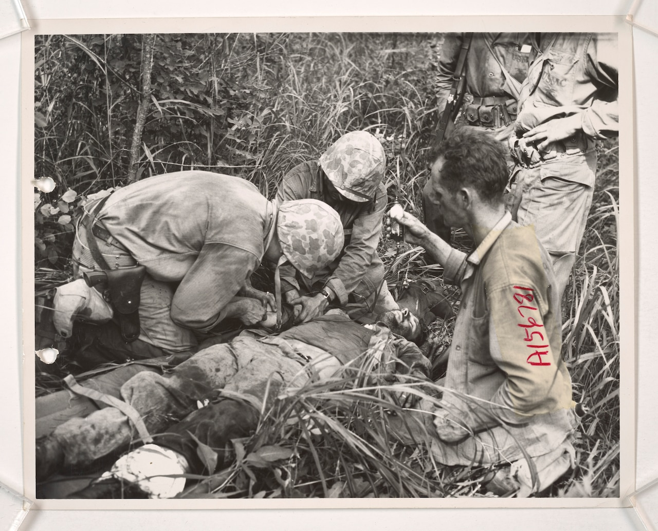 Three men in military uniforms work on an injured serviceman lying down in tall grass.