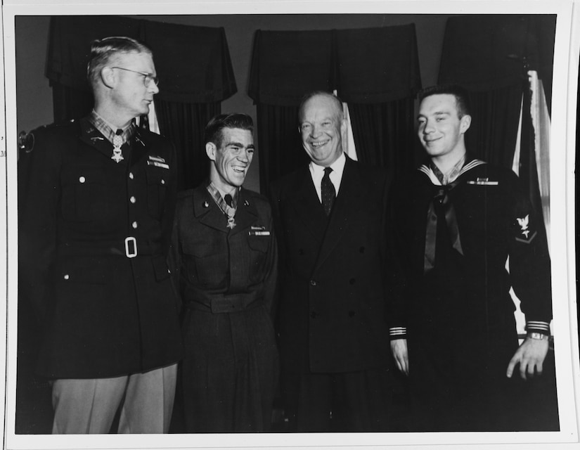 Four men, three in uniforms and wearing medals stand smiling.