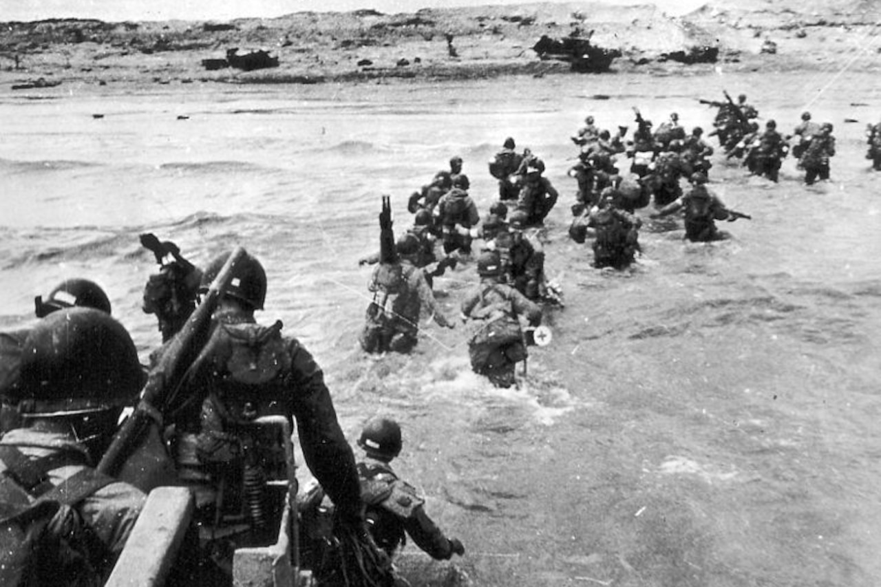 In a historic photo, a group of soldiers in combat gear wades through the hip-deep water as they head to a shoreline.