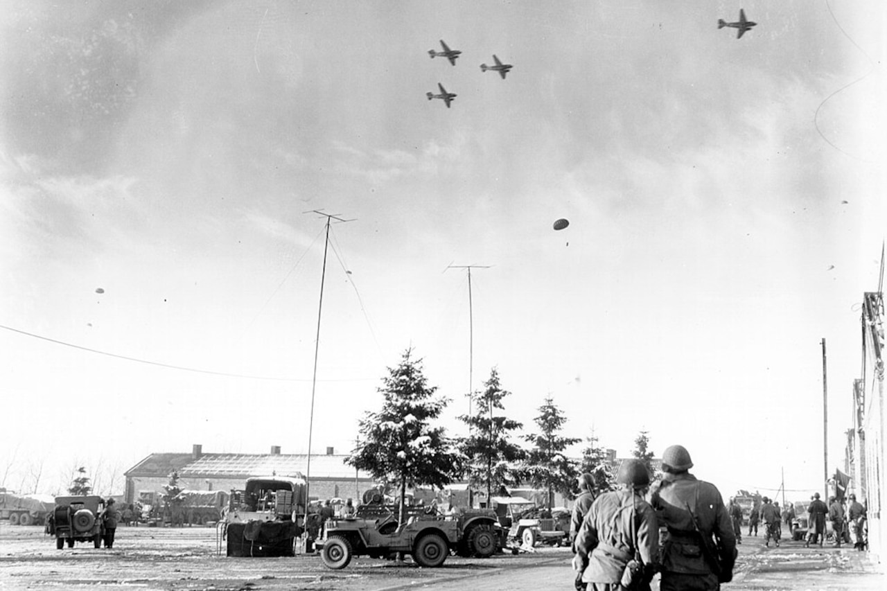In a historic photo, soldiers on the ground watch as paratroopers descend from the planes flying above them.