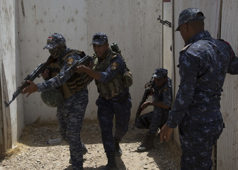 Four members of the Iraq Federal Police conduct an exercise.