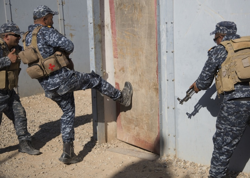 A member of the Iraq Federal Police kicks in a door as two other police men back him up during training in Iraq.