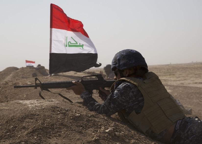A member of the Iraq Federal Police aims a gun.