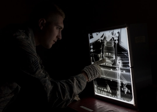 Staff Sgt. Tanner Wentworth, a Nondestructive Inspection Technician of the 101st Air Refueling Wing, Bangor Maine, studies an x-ray, June 25, 2018. The x-rays help detect faults in aircraft and equipment.