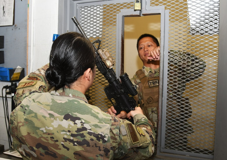 A photo of an Airman handing a weapon to another Airman.