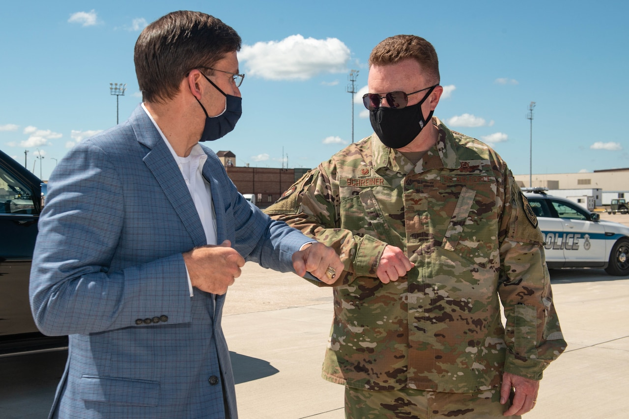 Two men, one in a military uniform, the other in a suit, bump elbows.