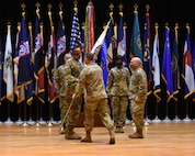 five soldiers pass a flag.