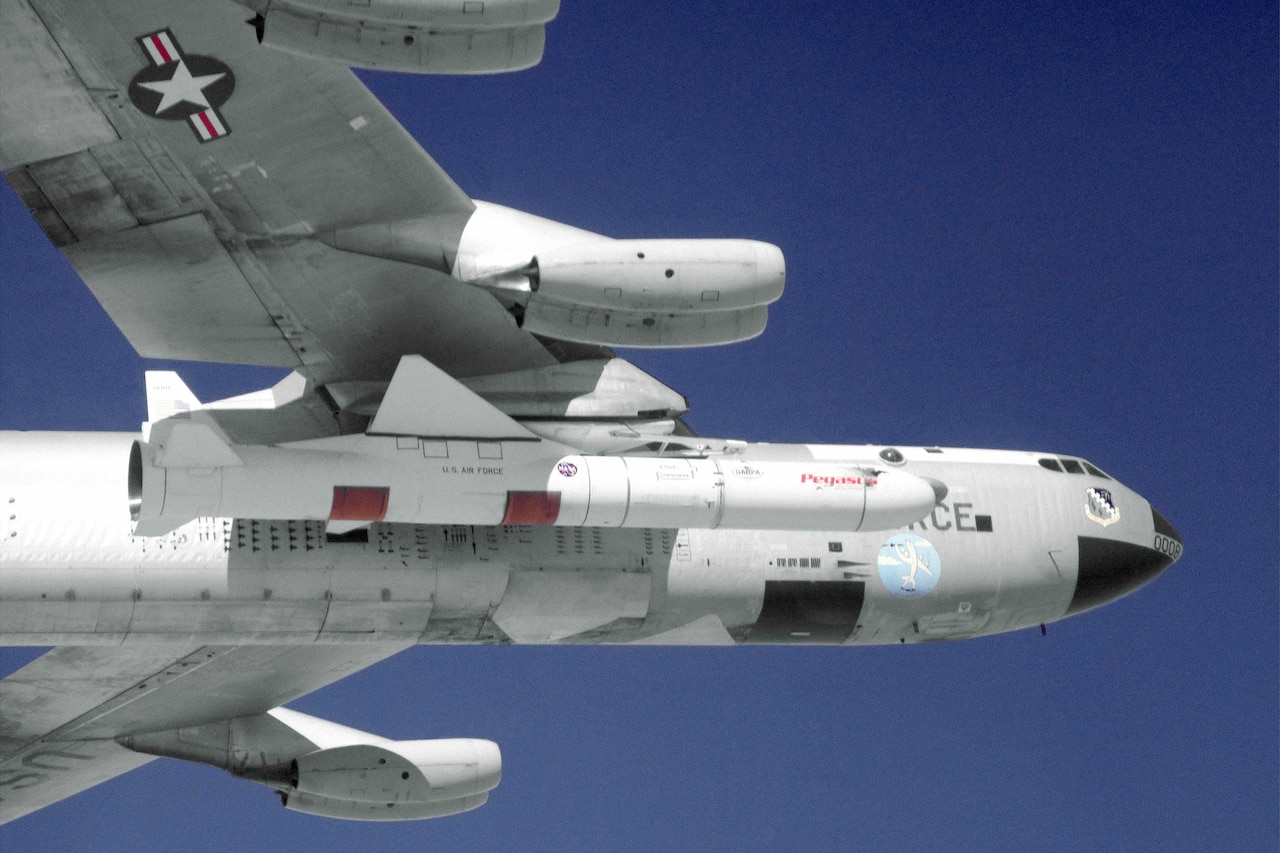 The underside of an aircraft is seen against a blue sky. A missile is attached to the underside of the wing.