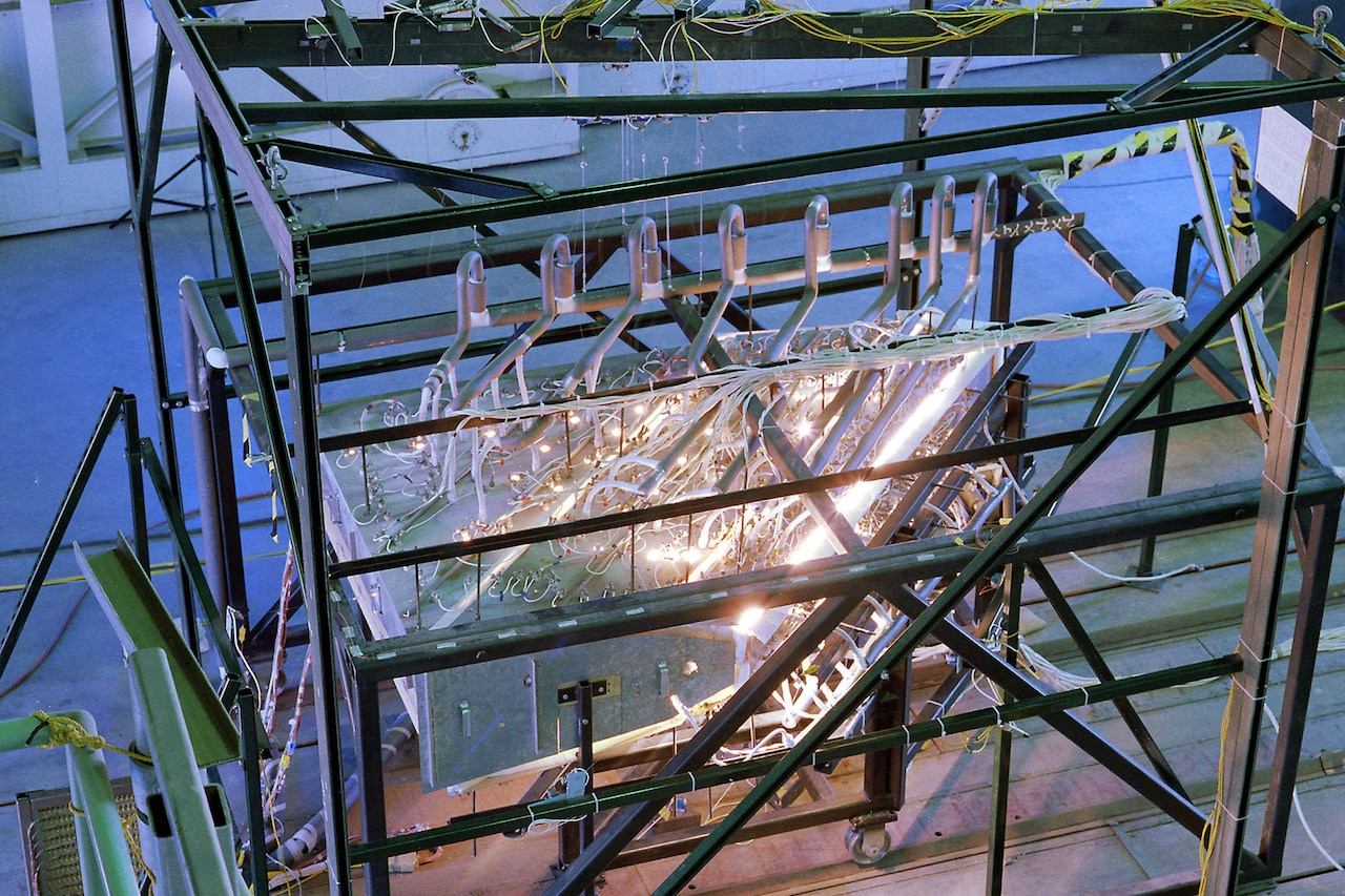 Coils and bright lights can be seen atop equipment that is inside a glass-paneled metal frame.
