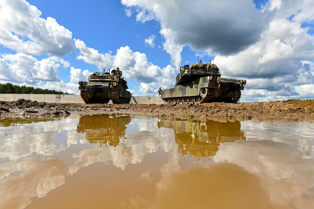 Two tanks sit in a muddy field, their images reflected in a puddle.