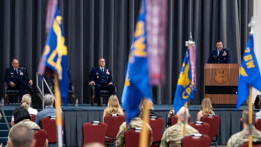 Maj. Gen. Mark E. Weatherington, 8th Air Force and Joint-Global Strike Operations Center commander, and Col. Michael A. Miller, outgoing 2nd Bomb Wing commander, listen to Col. Mark C. Dmytryszyn, incoming 2nd BW commander, address the crowd during a change of command ceremony at Barksdale Air Force Base, La., July 23, 2020. A change of command is a military tradition that represents a formal transfer of authority and responsibility for a unit from one commanding or flag officer to another. (U.S. Air Force photo by Airman 1st Class Jacob B. Wrightsman)