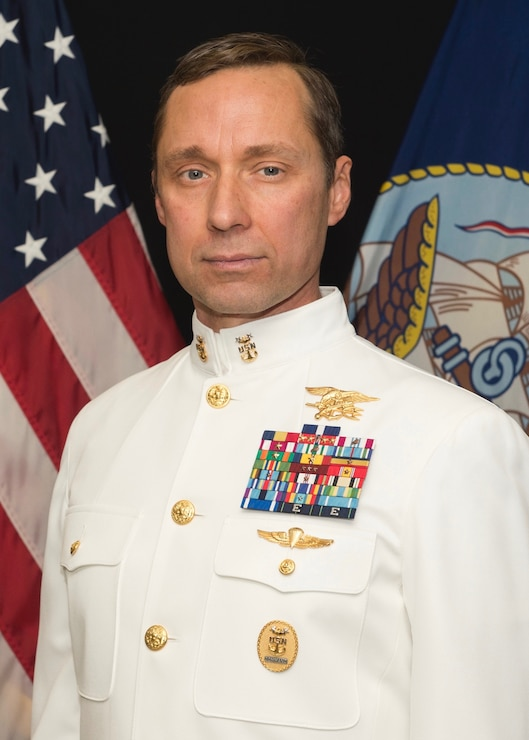 Britt Slabinski posing for the portrait with american and navy flags in the background