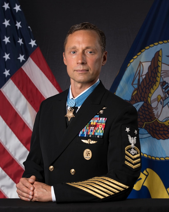 Britt Slabinski in uniform posing for the portrait with american and navy flags in the background
