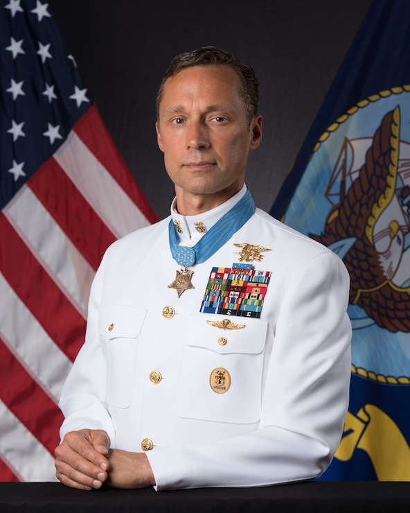 Britt Slabinski in uniform with medal of honor posing for the portrait with american and navy flags in the background