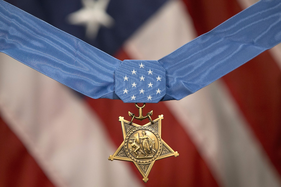 Britt Slabinski's medal of honor with american flag in the background