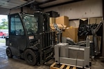 Airman 1st Class Krystal Bartling, 22nd Logistics Readiness Squadron flight services center journeyman, lifts a pallet of equipment to be processed July 16, 2020, at McConnell Air Force Base, Kansas. Last year the 22nd LRS flight services center repurposed $2.5 million in assets back into the DoD's operational budget.  (U.S. Air Force photo by Airman 1st Class Marc A. Garcia)
