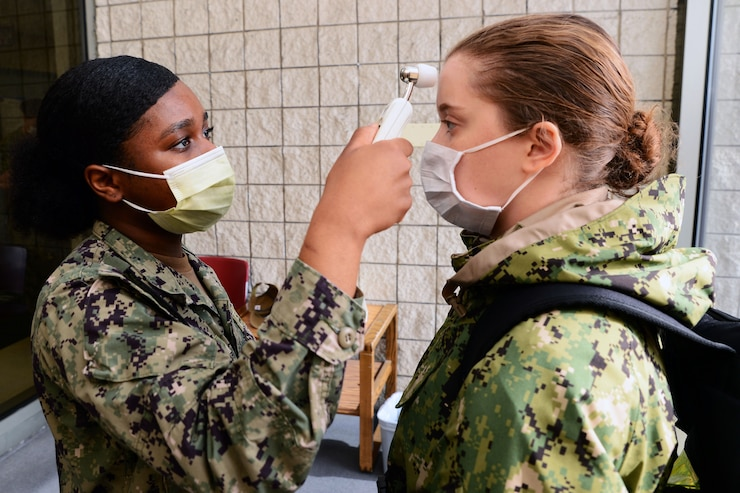 A service member wearing a face mask takes the temperature of another service member who is wearing a face mask.