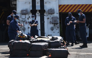 Members of the Coast Guard Cutter Stratton (WMSL-752) prepare to offload marijuana seized in international waters of the Eastern Pacific Ocean in June 2020. The crew aboard the Stratton disrupted the movement of nearly 6,000 pounds of cocaine, worth an estimated $102 million, during their patrol. (Coast Guard photo by Petty Officer 3rd Class Alex Gray)