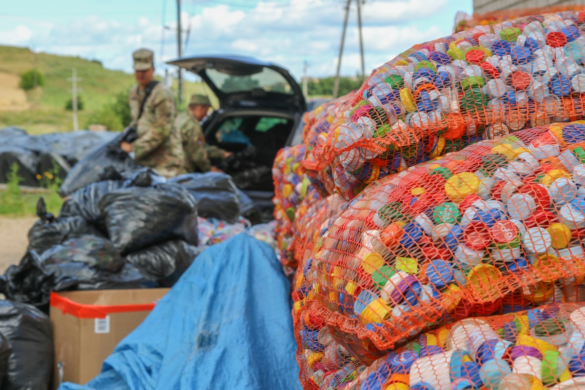 Soldiers unload bags of bottle caps.