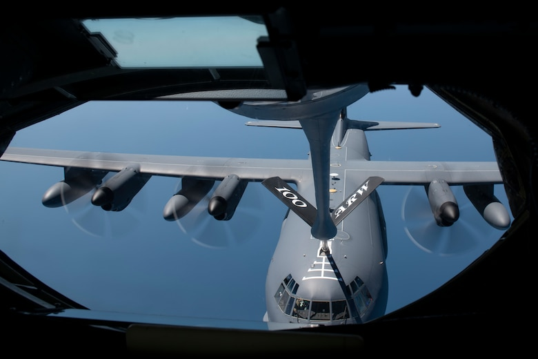 Military cargo plane being refueled, mid-air.