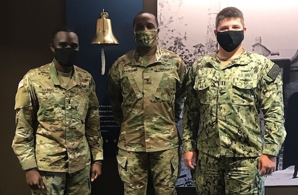 DLA Troop Support Commander Army Brig. Gen. Gavin Lawrence is flanked by 1st Lt. Brett Harris, left, and Navy Lt. Junior Grade Kevin Marvel, right, incoming and outgoing Aide de Camp to the Commanders, respectively, July 23, 2020 in the organization's headquarters building in Philadelphia.