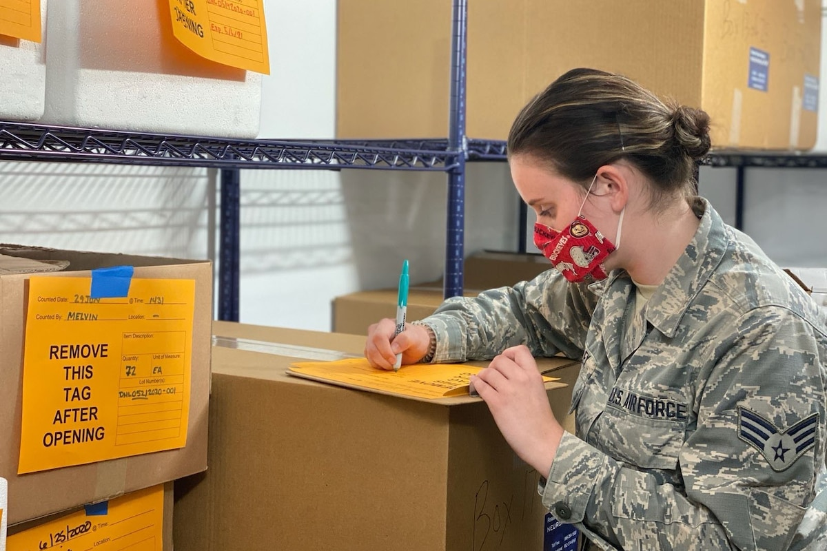 A guardsman wearing a mask checks a list of a shipment of personal protective equipment.