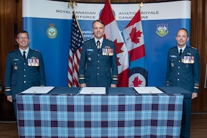 (From left) Incoming 1 Canadian Air Division/Canadian NORAD Region Commander Major-General Eric Kenny, Royal Canadian Air Force Commander Lieutenant-General Al Meinzinger, and outgoing 1 CAD/CANR Commander Lieutenant-General Alain Pelletier prepare to sign 1 CAD Change of Command scrolls during a ceremony at 17 Wing Winnipeg, Manitoba, July 6, 2020.