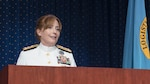 Woman in white Navy dress uniform speaks at a podium with the Defense Logistics Agency flag in the background.