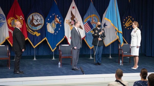 Two men in suits, a uniformed soldier and a woman in a Navy dress uniform stand on a stage with flags representing DLA and the military services.