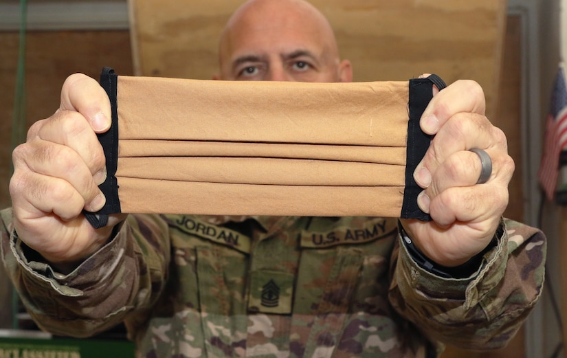U.S. Army 1st Sgt. Richard F. Jordan, 248th Medical Company (Area Support), shows off one of the estimated 2,000 handmade cloth masks sent from the United States to the unit at Al Asad Air Base, Iraq, on May 13, 2020. Troops and civilians at the base were able to use the masks to help prevent the spread of COVID-19. Coalition Forces remain united and determined in their mission to degrade and defeat Daesh. (U.S. Army by Sgt. 1st Class Gary A. Witte)