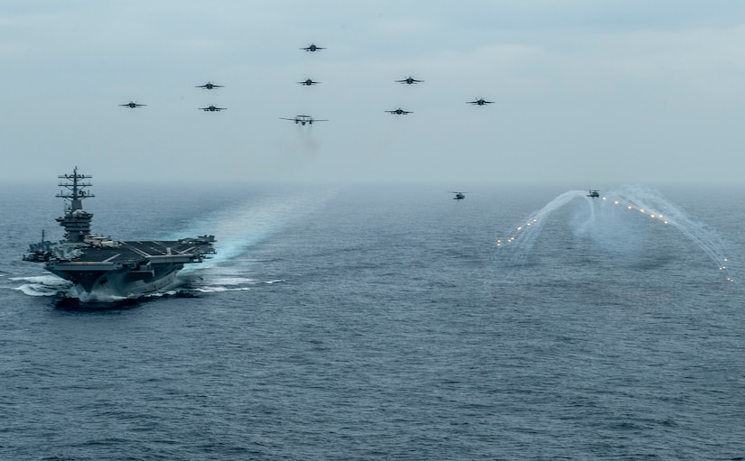 """200602-N-VW723-1416 PACIFIC OCEAN (June 2, 2020) Aircraft from Nimitz Carrier Strike Group fly in formation over the aircraft carrier USS Nimitz (CVN 68) while an MH-60S Sea Hawk helicopter, from the """"Battle Cats"""" of Helicopter Maritime Strike Squadron (HSM) 73. Nimitz is underway conducting composite training unit exercise (COMPTUEX). COMPTUEX is an intensive exercise designed to fully integrate units of the carrier strike group, while testing a strike group's ability as a whole to carry out sustained combat operations from the sea. (U.S. Navy photo by Mass Communication Specialist 3rd Class Keenan Daniels/Released)"""