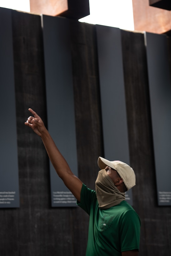 An Air Force Reserve Officer Training Corps cadet training assistant looks up and points at one of the suspended monuments at The National Memorial for Peace and Justice.