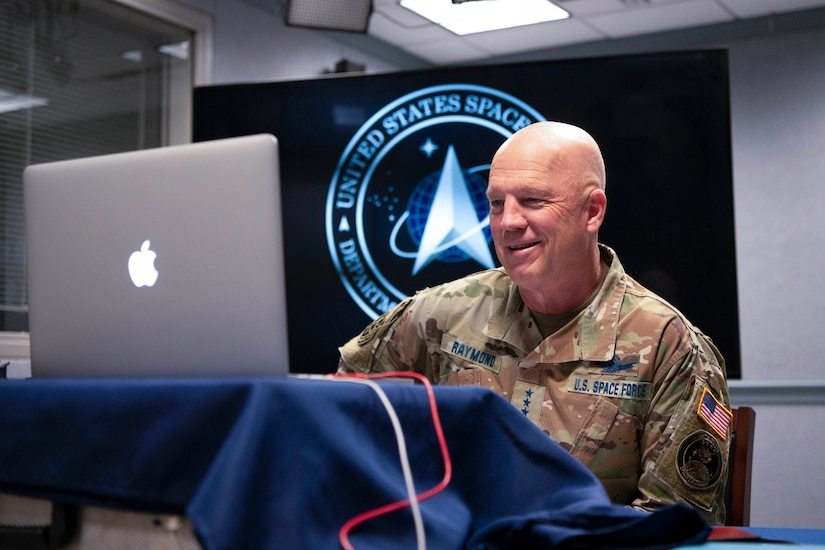 Man in a military uniform participates in a virtual face-to-face call via laptop.