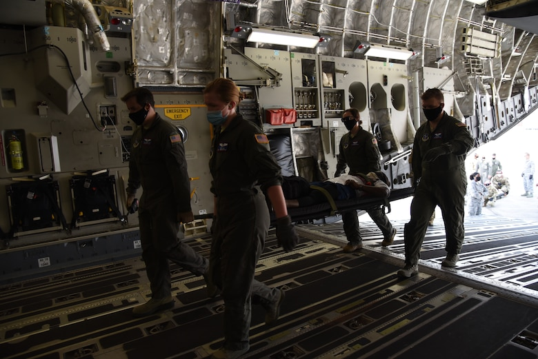 Reserve Citizen Airmen from the 36th Aeromedical Evacuation Squadron and Mississippi Air National Guardsmen from the 183rd AES work together loading patients into a C-17 Globemaster III during a three-day training event, July 20-22, 2020 at Keesler Air Force Base and the Mississippi Air National Guard's Combat Readiness Training Center in Gulfport, Mississippi. The training was a joint effort between Reservists and Guardsmen to work as one team, while training on patient care and handling during a simulated air evacuation of injured service members. (U.S. Air Force photo by Jessica L. Kendziorek)