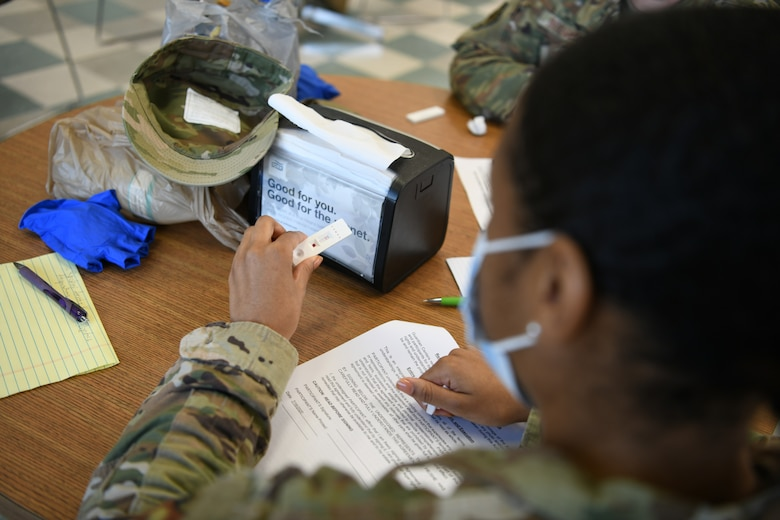 Photo shows a woman holding a test in her hand waiting on results.