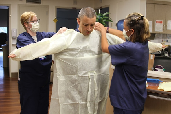 Two Air Force nurses wearing masks help another Airman with putting on personal protective equipment.