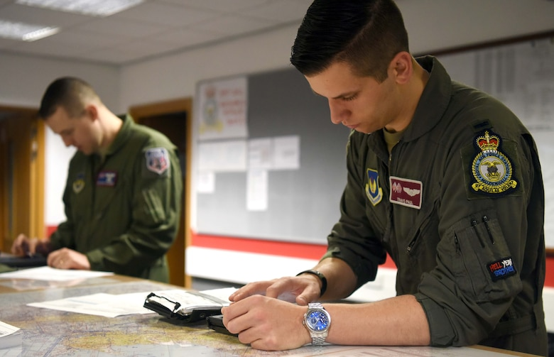 First Lieutenant Travis Paul, 351st Air Refueling Squadron pilot, right, and Tech. Sgt. Grant Ringenberg, 351st ARS boom operator, review flight plans at RAF Mildenhall, England, July 23, 2020. The 351st ARS provides operational air refueling, aeromedical evacuation, airlift and rapid contingency response options for U.S. and NATO fighter, bomber and support and reconnaissance aircraft in the European and African theater of operations. (U.S. Air Force photo by Senior Airman Brandon Esau)