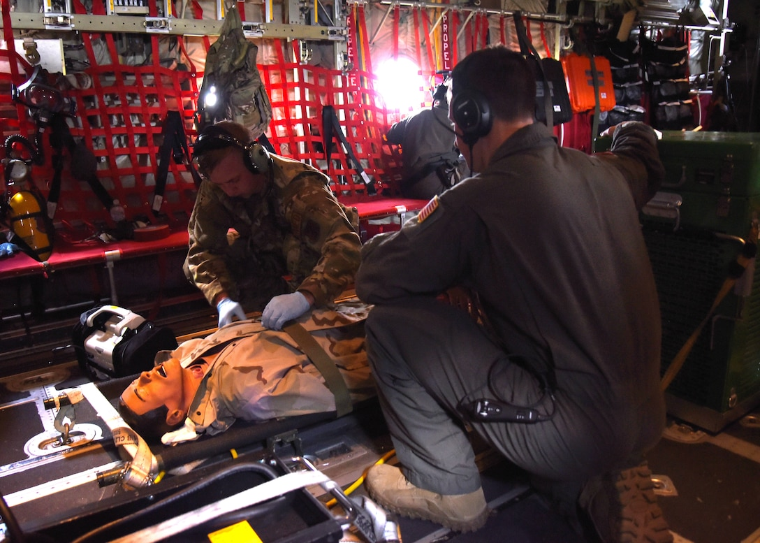Tech Sgt. David McAlpin and Airman 1st Class Zachary Winstead, 183rd Aeromedical Evacuation Squadron medical technicians, check the vitals of the medical mannequin during a training flight on the C-130J Super Hercules during a three-day training event, July 20-22, 2020 at Keesler Air Force Base and the Mississippi Air National Guard's Combat Readiness Training Center in Gulfport, Mississippi. Reserve Citizen Airmen from the 36th AES and Mississippi Air National Guardsmen from the 183rd AES united for joint training to work as one team. They trained on patient care and handling during a simulated air evacuation of injured service members. (U.S. Air Force photo by Jessica L. Kendziorek)