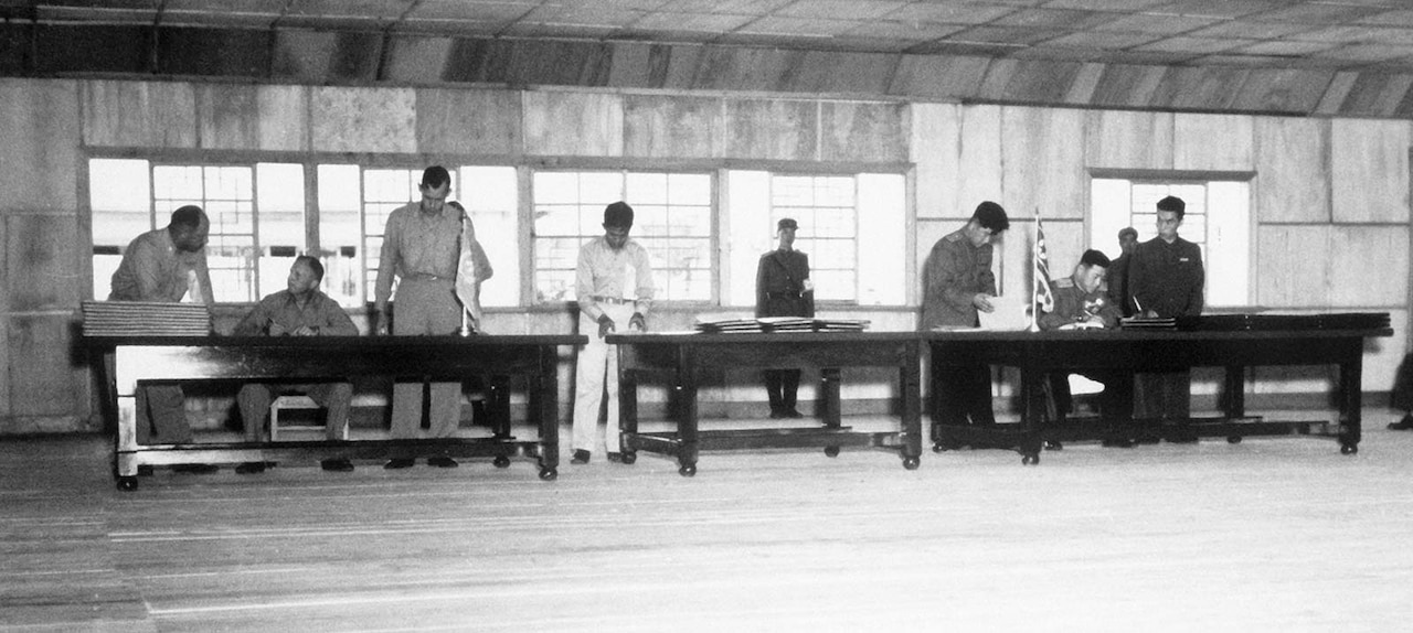 People sit and stand behind three, long tables as guards stand in the background.
