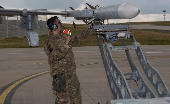 U.S. Air Force Staff Sgt. Zachary Ward, 52nd Aircraft Maintenance Squadron load crew team chief, mounts an inert AIM-120 air-to-air to an F-16 Fighting Falcon during an Integrated Combat Turn exercise at Spangdahlem Air Base, Germany, July 17, 2020. Ward ensured the missile properly mounted to the aircraft and then engaged the detent to ensure the missile remained mounted to the aircraft. (U.S. Air Force photo by Senior Airman Kyle Cope)
