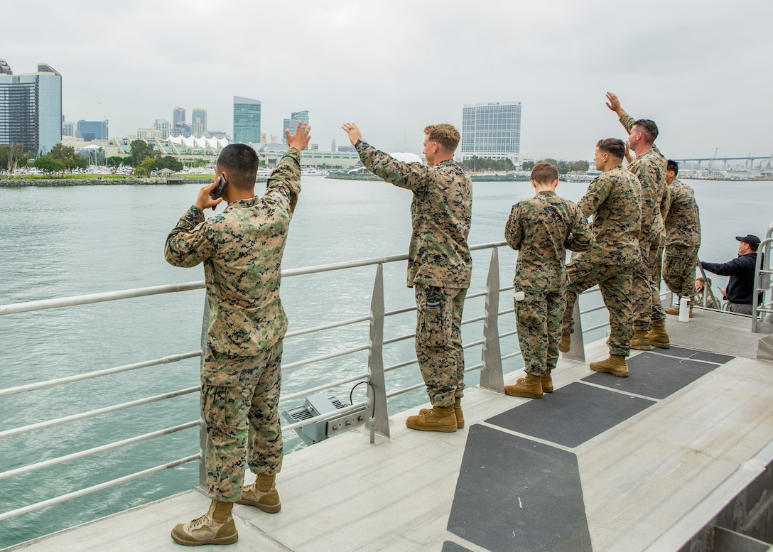 U.S. Marines and Sailors wave from a distance to their friends and family as they depart San Diego, Calif. aboard USNS City of Bismarck (EPF-9) July 2.