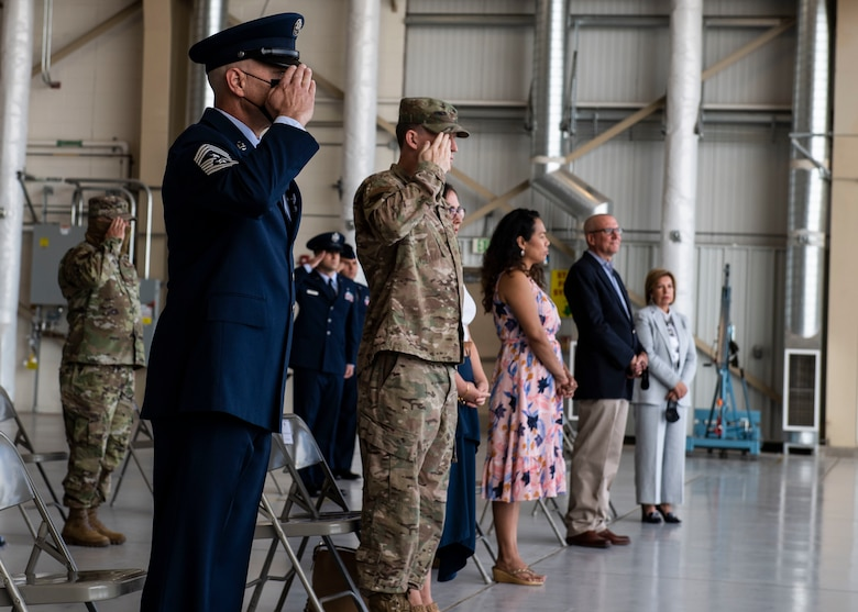 U.S. Air Force Airmen and families stand for the arrival of the official party.