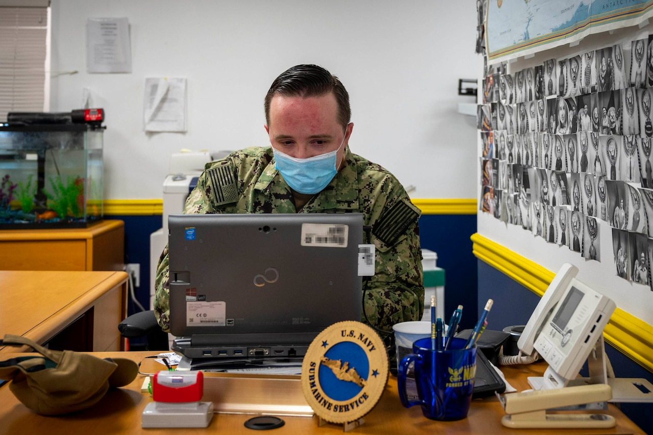 Masked sailor works on laptop.