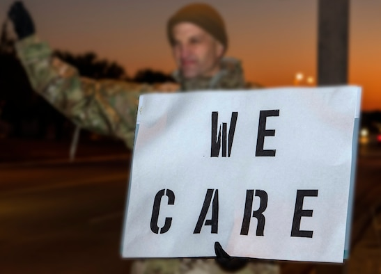"""Lt. Col. Scott Christensen, 331st Training Squadron commander, holds a positive message of support at a base gate during the morning inbound commute as part of their new initiative, """"We Care,"""" at Joint Base San Antonio-Lackland, Texas."""