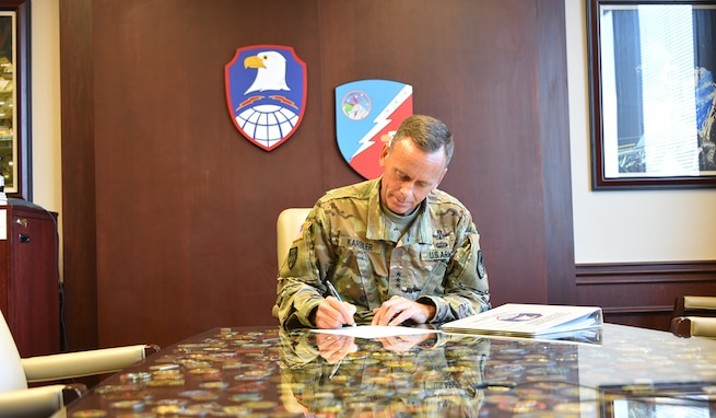 Lt. Gen. Daniel L. Karbler, commanding general, U.S. Army Space and Missile Defense Command, signs an official memorandum regarding the command's new Cost Management Guide. The guide was created by the command's G-8 team as a resource providing tools and methodologies for units and directorates to maximize their capabilities during a time of fiscal uncertainty. (U.S. Army photo by Lira Frye)