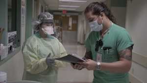 Cesar De La Vega (left) ensures Maj. Kay Bolin properly dons her personal protective equipment in an intensive care unit at Brooke Army Medical Center. (U.S. Army photo by James Camillocci)