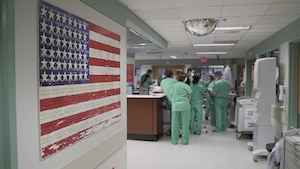 Brooke Army Medical Center nurses conduct a shift change briefing in a COVID-19 intensive care unit, July 17, 2020. (U.S. Army photo by James Camillocci)
