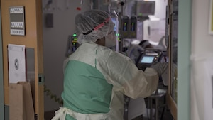 April Pace, a registered nurse, enters a patient room in a COVID-19 intensive care unit at Brooke Army Medical Center, July 17, 2020. (U.S. Army photo by James Camillocci)
